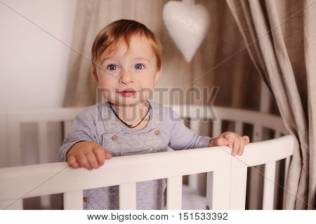 cute happy baby boy awake in his bed in the morning and playing. Candid capture in real life interior