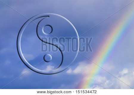 The symbol of Yin -- Yang in the background of sky and rainbow .