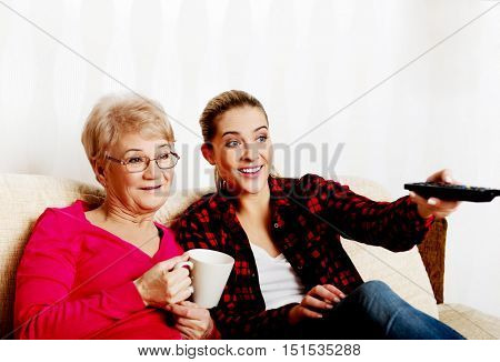 Portrait of granddaughter and grandmother sitting on couch and watching TV