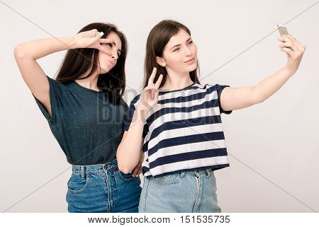 Positive friends portrait of two happy sister girls making selfie, funny faces, grimaces, joy, emotions, casual style on light grey background