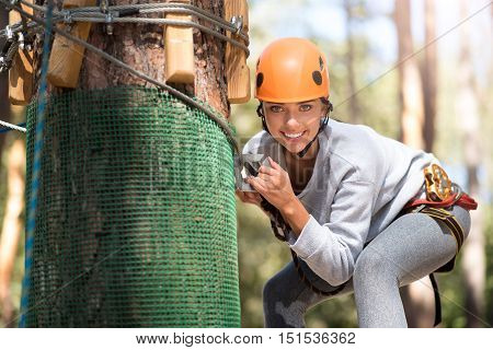 Fully equipped. Attractive cute young woman wearing protective helmet and mountain carabiner while following her rope way
