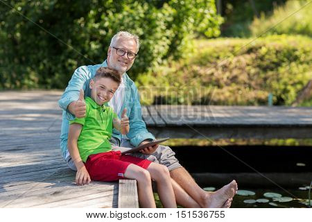 family, generation, technology, communication and people concept - grandfather and grandson with tablet pc computer sitting on river berth