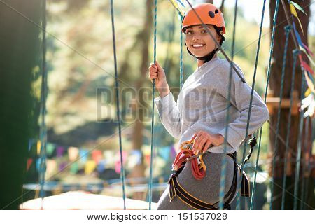 Wonderful time. Cute good looking slender woman holding on to the carabiner and smiling while having fun in the high wire park