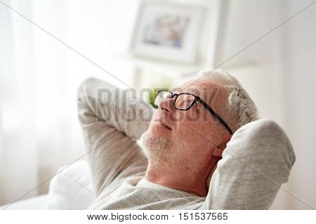 old age, comfort and people concept - smiling senior man in glasses relaxing on sofa at home