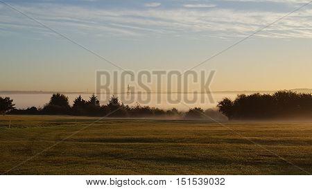 misty dawn with a pylon peeking through