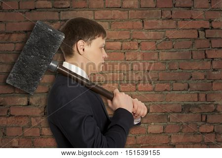 Determined businessman with hammer in hands on the background wall