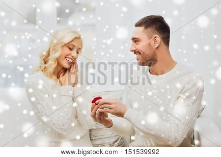 love, couple, relationship, proposal and holidays concept - happy man giving engagement ring in little red gift box to woman at home