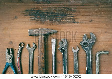 Hammer pliers and wrenches old on a wooden board