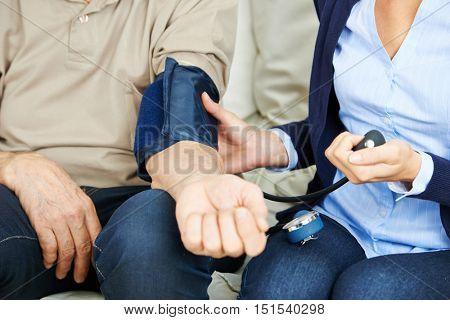 Woman checking blood pressure of senior man in nursing home