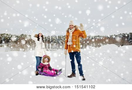 parenthood, fashion, season, gesture and people concept - happy family with child on sled walking and waving hand in winter outdoors