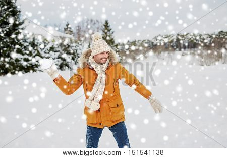 people, season and leisure concept - happy young man playing snowballs in winter