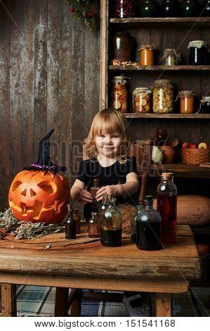 Little cute witch in a black dress fun about magic items