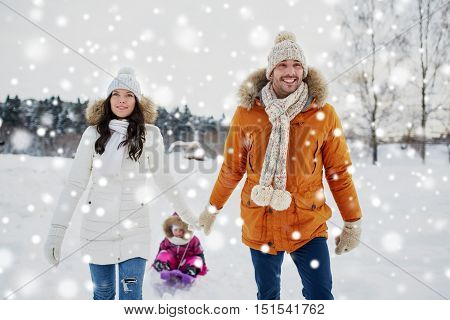 parenthood, fashion, season and people concept - happy family with child on sled walking in winter outdoors