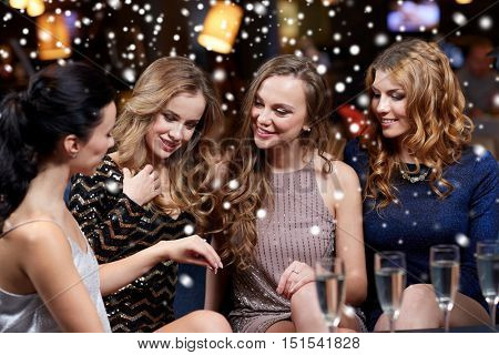 christmas, friends, bachelorette party and winter holidays concept - happy woman showing engagement ring to her friends with champagne glasses at night club over snow