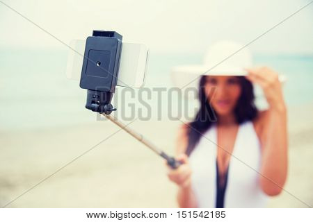 lifestyle, leisure, summer, technology and people concept - close up of smiling young woman or teenage girl in sun hat taking picture with smartphone on selfie stick on beach