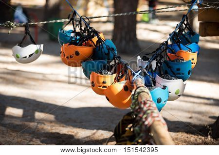 Ready to be used. Close up of special helmets of different colors hanging in a row on the rope