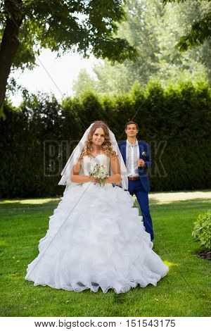 Newlyweds pose in the park on a warm sunny day