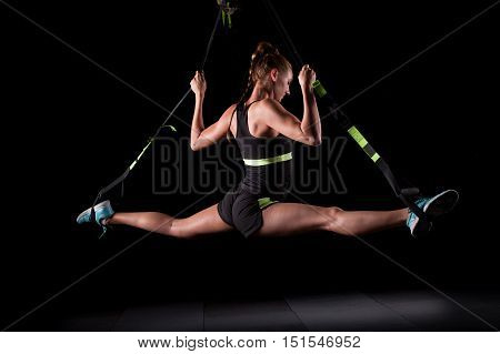 One young attractive woman does splits crossfit stretching with straps Total Resistance eXercises fitness straps in the gym's studio on black background