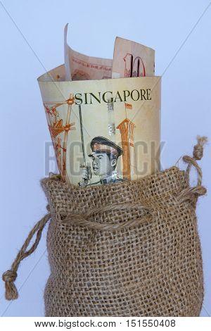 Singaporean dollars in a brown hessian bag.