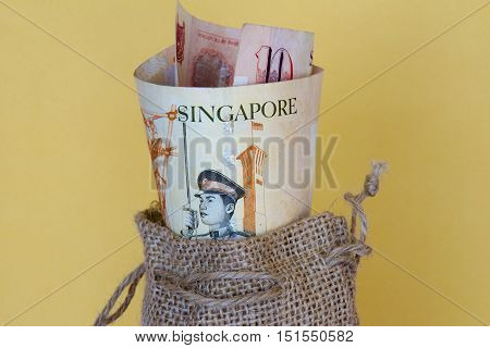 A bunch of Singaporean dollars in a sack.