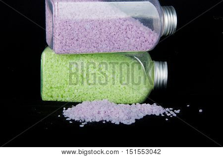 Heap of purple sea salt grains for bath and two transparent bottles with green and violet grains inside on black background