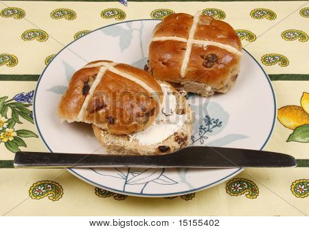 Buttered hot cross bun on a plate