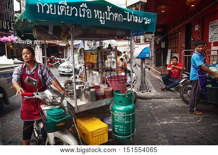 Pattaya Thailand - March 28 2016: Asian woman driving a food cart selling street food. Mobile Thai food vendor. Text on a cart: Noodles with pork chicken pumpkin.
