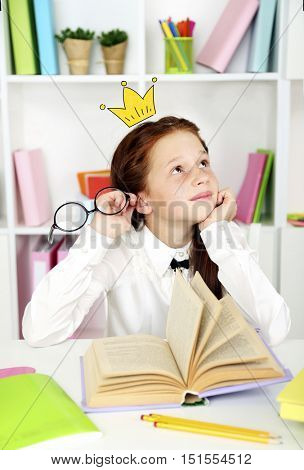 Cute little girl with princess crown drawing above head studying at classroom.