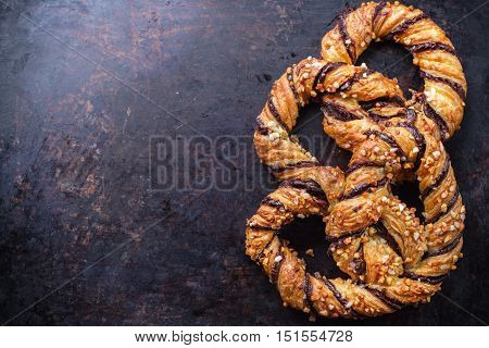 Homemade sweet pretzel with chocolate and crunchy almonds, traditional german bavarian treat on a black rusty table. Selective focus, copy space background, top view overhead flat lay