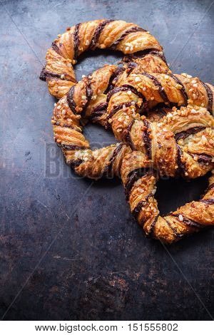 Homemade sweet pretzel with chocolate and crunchy almonds, traditional german bavarian treat on a black rusty table. Selective focus, copy space background