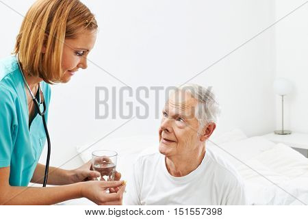 Old man getting medicine and water from nurse in nursing home
