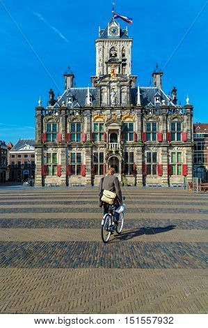 Delft, Netherlands - April 4, 2008:  Young Man Rides A Bicycle Near Council Building (stadhuis)