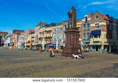 Delft, Netherlands - April 4, 2008:  A Young Girl With A Dog Sitting Near Hugo Grotius Statue