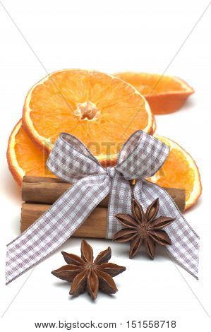 Slices of dried orange with star anise and cinnamon sticks isolated against white