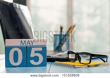 May 5th. Day 5 of month, calendar on business office background, workplace with laptop and glasses. Spring time, empty space for text.