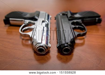 Black and silver pistols on a table