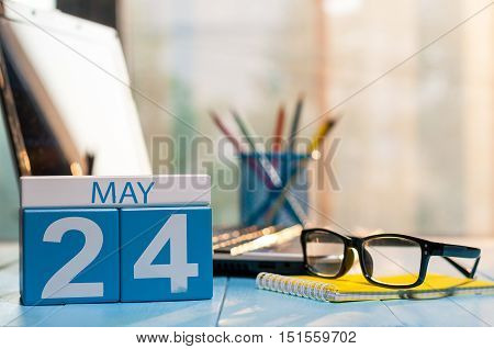 May 24th. Day 24 of month, calendar on business office background, workplace with laptop and glasses. Spring time, empty space for text.