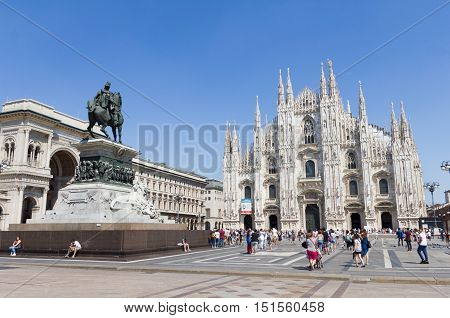 MILAN, ITALY - AUGUST 13, 2016 : Tourists walking in front of the Duomo in Milan. The main city landmark is the 5th largest church in the world and the second in Italy.