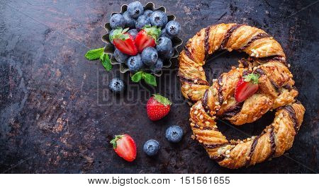 Homemade sweet pretzel with chocolate, crunchy almonds, berries, traditional german bavarian treat on a black rusty table. Selective focus, copy space background, top view overhead flat lay