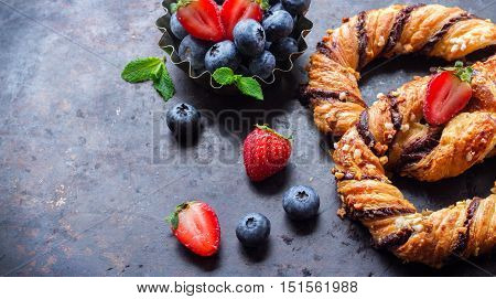 Homemade sweet pretzel with chocolate, crunchy almonds, berries, traditional german bavarian treat on a black rusty table. Selective focus, copy space background