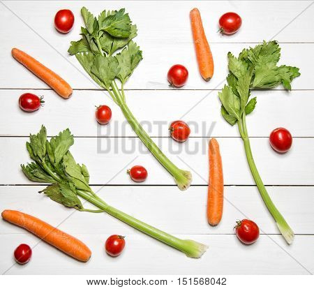 Fresh vegetables on white wooden table. Top view. Celery, carrot and tomatoes pattern