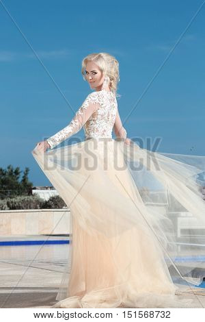 Elegant Bride In Fashion Wedding Dress Over Blue Sky. Attractive Young Blond Woman In Long Gown. Out