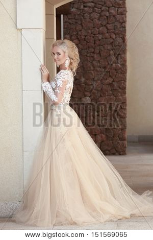 Elegant Bride In Fashion Wedding Dress Posing By The Wall. Attractive Young Blond Woman In Long Gown