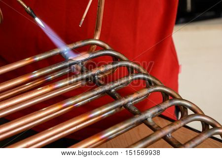 A skilled worker connects copper pipes to the braze - close-up