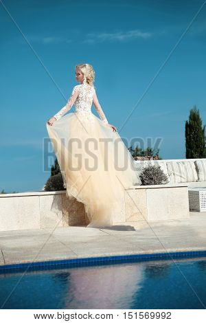 Beautiful Bride In Gorgeous  Wedding Dress With Blowing Skirt Walking By Water Over Blue Sky, Outdoo