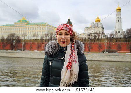 Woman stands near river, Grand Kremlin Palace nad Kremlin walls in Moscow at sring
