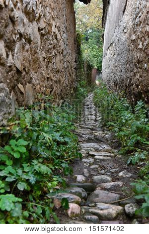 Narrow Village Alley With Stone Walls