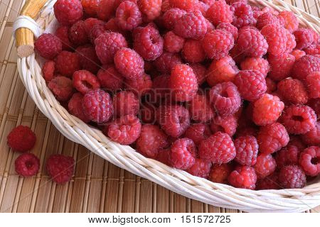 Lots of fresh raspberries laid out in a wooden basket, standing on a wooden table.