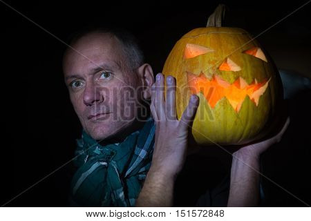 Man with glowing pumpkin peering into the darkness at halloween night.