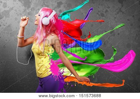 Young woman listening to music in headphones. Colorful design on dark background.
